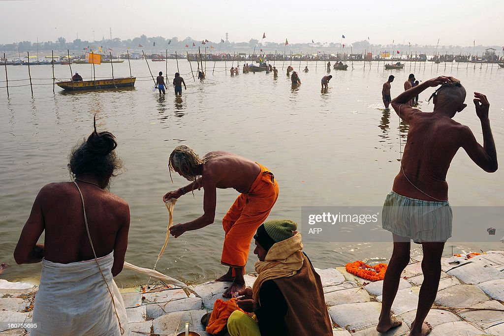 Hindu devotees take a dip at the confluence of the Rivers Ganges, Yamuna and mythical Saraswati during the Maha Kumbh festival in Allahabad on February 5, 2013. The Kumbh Mela in the town of Allahabad will see up to 100 million worshippers gather over 55 days to take a ritual bath in the holy waters, believed to cleanse sins and bestow blessings. AFP PHOTO/Sanjay KANOJIA
