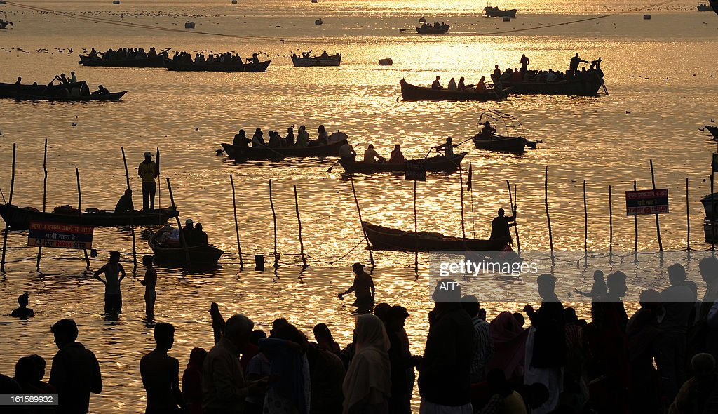 Hindu devotees take a holy dip at the Sangam or the confluence of the Yamuna, Ganges and mythical Sarawati rivers at sunrise during the Maha Kumbh festival in Allahabad on February 12, 2013. The Kumbh Mela in the town of Allahabad will see up to 100 million worshippers gather over 55 days to take a ritual bath in the holy waters, believed to cleanse sins and bestow blessings.