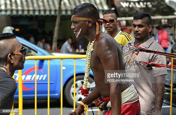 Hindu devotees take part in a procession to celebrate the annual Thaipusam festival in the Little India district of Singapore on January 24 2016...