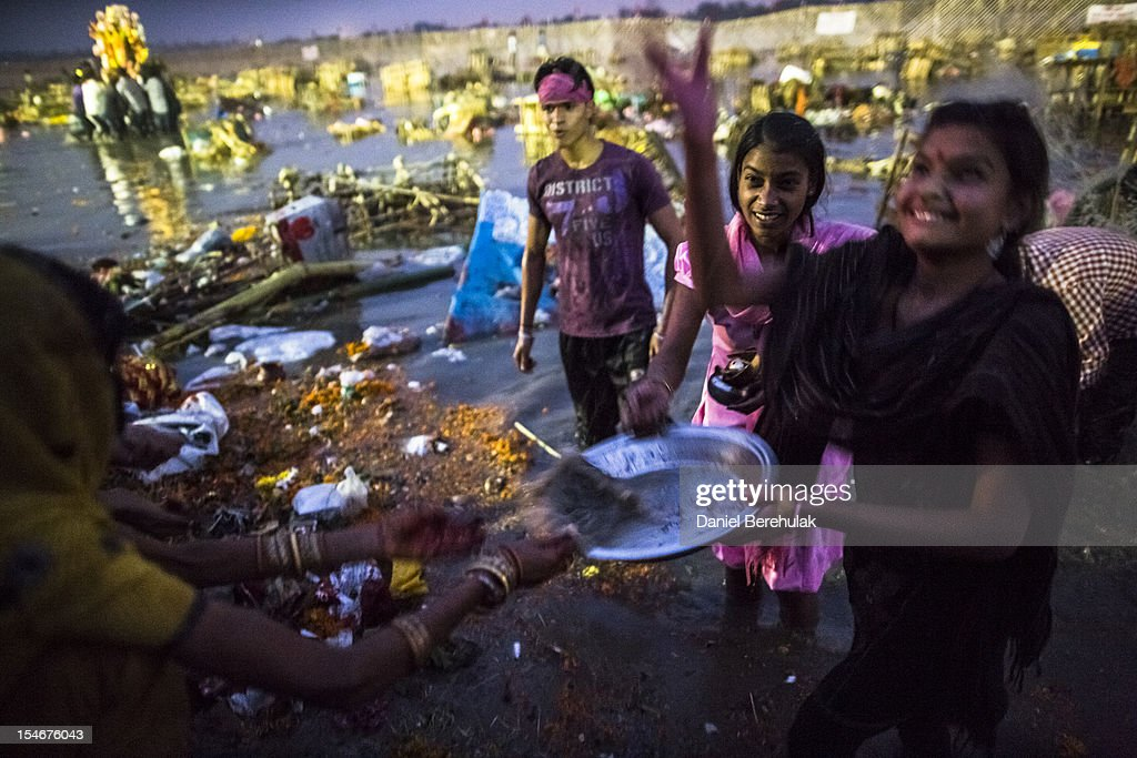 Hindu devotees throw water considered to be holy after having immersed an idol of Goddess Durga into the Yamuna river on the last day of the Durga Puja festival on October 24, 2012 in Delhi, India. The festival celebrates the worship of the Hindu Goddess Durga, who in Hindu Mythology is celebrated as the Goddess of power and the victor of good over evil.
