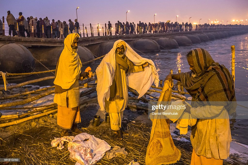 Hindu devotees undress before taking a dip on the banks of Sangam, the confluence of the holy rivers Ganges, Yamuna and the mythical Saraswati, during the Maha Kumbh Mela on February 12, 2013 in Allahabad, India. The Maha Kumbh Mela, believed to be the largest religious gathering on earth is held every 12 years on the banks of Sangam, the confluence of the holy rivers Ganga, Yamuna and the mythical Saraswati. The Kumbh Mela alternates between the cities of Nasik, Allahabad, Ujjain and Haridwar every three years. The Maha Kumbh Mela celebrated at the holy site of Sangam in Allahabad, is the largest and holiest, celebrated over 55 days, it is expected to attract over 100 million people.
