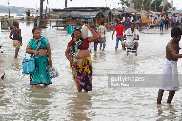 Hindu devotees walk from the flooded banks of river Ganga after heavy monsoon rains that caused the rise of water levels in Allahabad