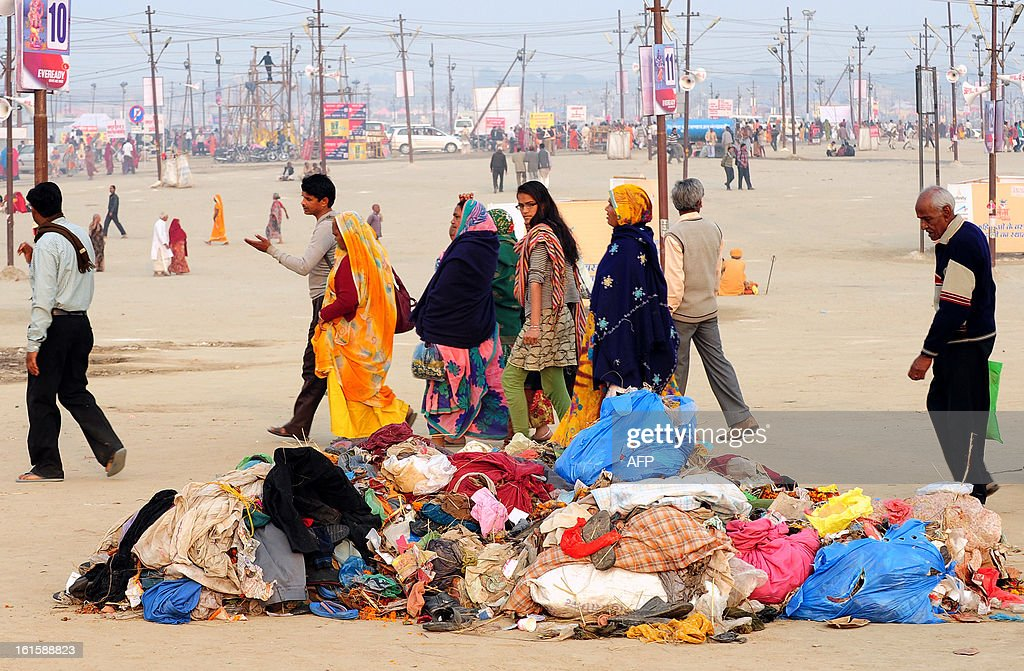 Hindu devotees walk past a pile of trash while returning from the river after taking a holy dip at the Sangam or the confluence of the Yamuna, Ganges and mythical Sarawati rivers at sunrise during the Maha Kumbh festival in Allahabad on February 12, 2013. The Kumbh Mela in the town of Allahabad will see up to 100 million worshippers gather over 55 days to take a ritual bath in the holy waters, believed to cleanse sins and bestow blessings.