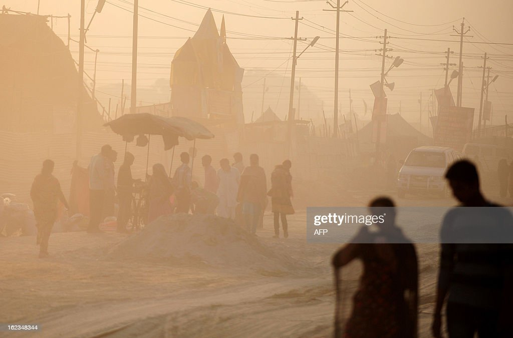 Hindu devotees walk through the dust at Sangam, the confluence of the Yamuna, Ganges and mythical Saraswati rivers and the site of the Kumbh Mela in Allahabad on February 22, 2013. The Kumbh Mela in the town of Allahabad will see up to 100 million worshippers gather over 55 days to take a ritual bath in the holy waters, believed to cleanse sins and bestow blessings.
