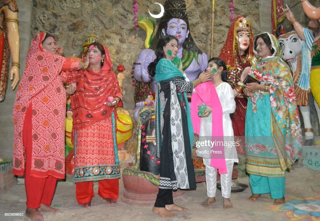 Hindu family celebrating there holy festival Holi at a local madnir of Hyderabad while putting color on each other.