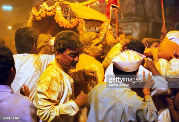Hindu Festival with turmeric being thrown over revellers wearing white clothes with a palanqin garlanded with flowers in the background Mumbai India...