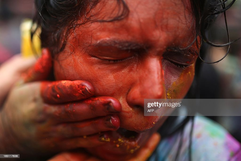 A Hindu girl grimaces as her friends smear coloured powders on her face to celebrate 'Holi' at a temple in Kuala Lumpur on March 31, 2013. Holi, the festival of colours where people smear each other with coloured powder and water, is celebrated by Hindus across the country.
