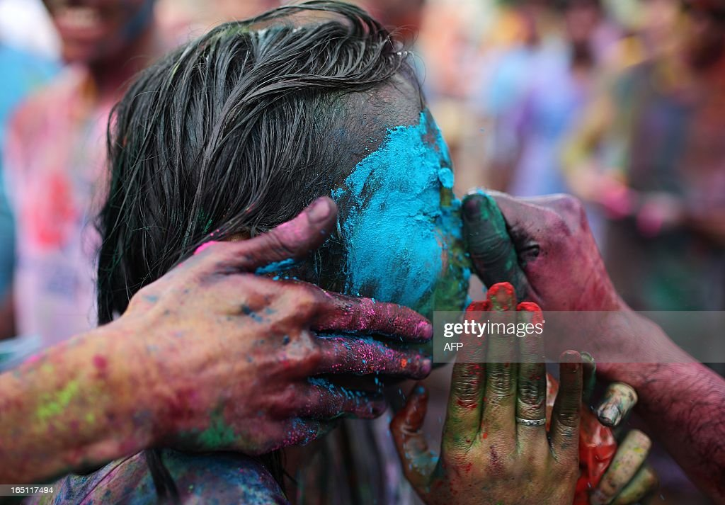 A Hindu girl grimaces as her friends smear her face with coloured powders to celebrate 'Holi' at a temple in Kuala Lumpur on March 31, 2013. Holi, the festival of colours where people smear each other with coloured powder and water, is celebrated by Hindus across the country. AFP PHOTO / MOHD RASFAN