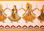 Hindu gods dancing on a fresco with colorful paints on carved wall of 19th century house in India. Naive art of India