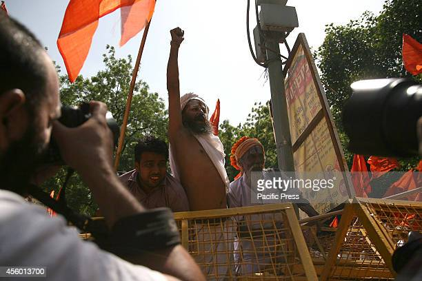 Hindu Holy Man holds slogan during a protest against 'Love Jihad' at New Delhi Love Jihad is an alleged activity under which young Muslim men...