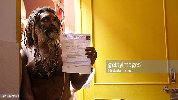 Hindu holy man stands with form of medical checkup before his registration for the annual pilgrimage to the Amarnath cave shrine on June 28 2014 in...