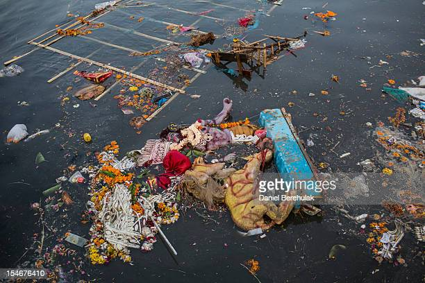 Hindu idols are seen immersed in the Yamuna river on the last day of the Durga Puja festival on October 24 2012 in Delhi India The festival...
