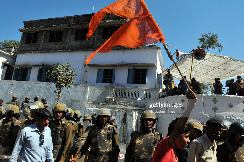 A Hindu kid raise a saffron flag as heavy force is deployed at Bhojshala on February 11, 2016 in Dhar, India. A communal flare-up is feared in the otherwise peaceful town of Dhar, Madhya Pradesh, on Friday, February 12. The contested site is the Kamal-al-Din congregational mosque also called Bhojshala is protected by the Archaeolgical Survey of India, which allows Muslims to offer jummah or Friday prayers. Hindus are allowed entry in the monument to offer prayers on Tuesdays and conduct a special puja on the occasion of Basant Panchami. This week, however, the Friday prayers coincide with the festival of Basant Panchami.
