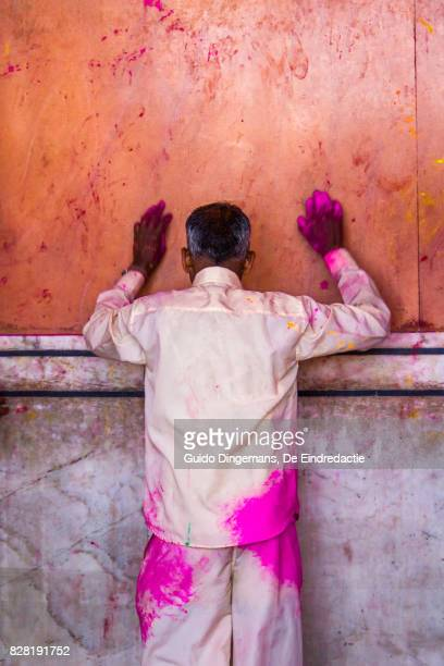 A hindu man covered in paint praying at the temple during the Holi Festival in Jaipur, India