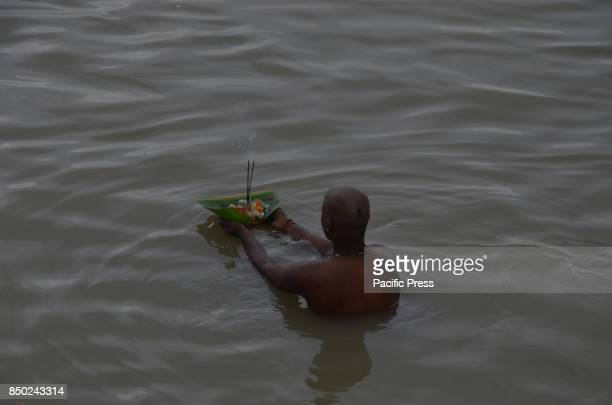 Hindu man perform Tarpana religious ritual on the bank of the river Ganges to honor the souls of his departed ancestors during the auspicious day of...