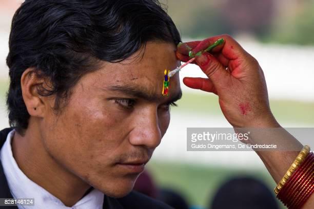 A hindu man receives a tika on his forehead during Bhai Tika (Tihar, Diwali) celebrations in Kathmandu, Nepal.