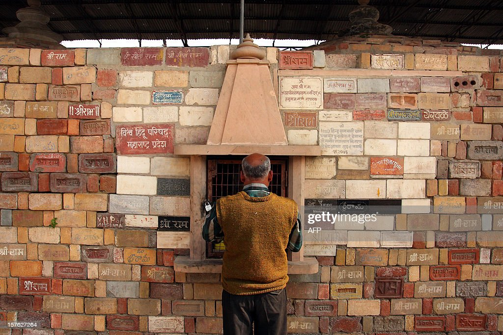 A Hindu man stands at a wall of bricks bearing the name of 'Shri Ram' at the Karsevak Puram workshop in Ayodhya on December 5, 2012, the eve of the 20th anniversary of the demolition of the Babri Masjid. India risked being torn apart by sectarian conflict 20 years ago when Hindu zealots demolished a mosque, triggering deadly riots, but analysts say economic growth has proved a quiet balm on tensions. AFP PHOTO/ Sanjay KANOJIA