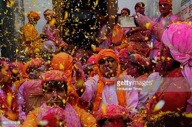 Hindu men from the village of Nandgaon throw flowers at each other as they sing before taking out a procession for the Lathmar Holi festival at...