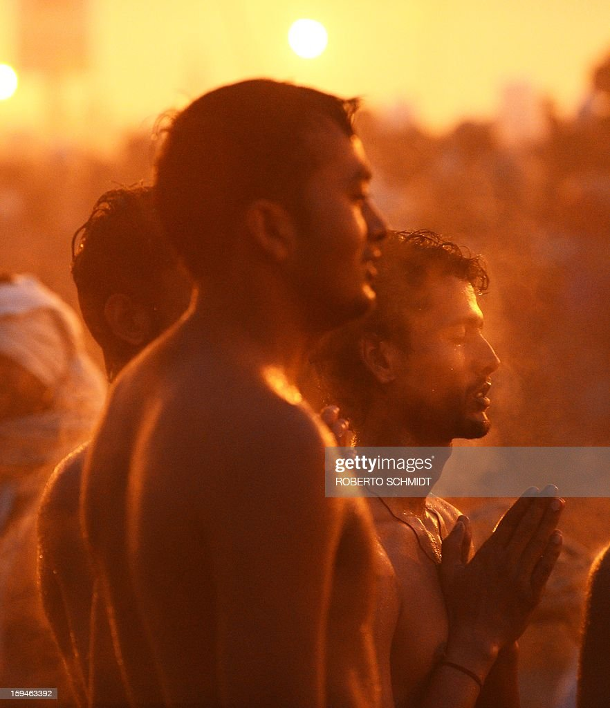 Hindu men pray as they bathe in the waters of the Sangham or the confluence of the the Yamuna and Ganges rivers during the Kumbh Mela in Allahabad on January 14, 2013. Hundreds of thousands of Hindu pilgrims led by naked, ash-covered holy men streamed into the sacred river Ganges on Monday at the start of the world's biggest religious festival. The Kumbh Mela in the Indian town of Allahabad will see up to 100 million worshippers gather over the next 55 days to take a ritual bath in the holy waters, believed to cleanse sins and bestow blessings. Before daybreak on Monday, a day chosen by astrologers as auspicious, hundreds of gurus, some brandishing swords and tridents, ran into the swirling and freezing waters for the first bath, signalling the start of events.AFP PHOTO/ROBERTO SCHMIDT
