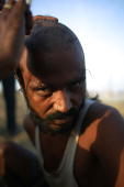 Hindu pilgrim has his head shaved in the style of a pundit at the ritual bathing site at Sangam the confluence of the Ganges Yamuna and mythical...