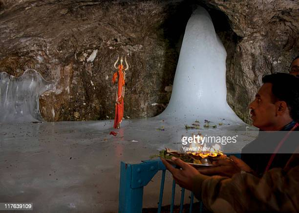 Hindu pilgrim worships in front of an ice stalagmite called a Shiva Lingam a stylized phallus worshiped by Hindus as a symbol of the god Shiva during...