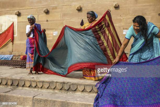 Hindu pilgrims dry sarees on the banks of the Ganges river in Varanasi Uttar Pradesh India on Saturday Oct 29 2017 A big drop in borrowing costs for...