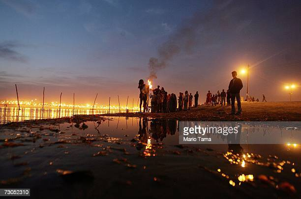 Hindu pilgrims perform a sunset ceremony at the ritual bathing site at Sangam the confluence of the Ganges Yamuna and mythical Saraswati rivers...