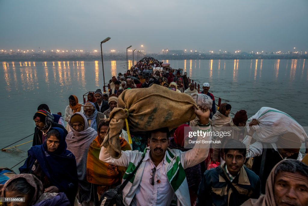 Hindu pilgrims walk across a pontoon bridge as others bathe on the banks of Sangam, the confluence of the holy rivers Ganges, Yamuna and the mythical Saraswati, during the Maha Kumbh Mela on February 12, 2013 in Allahabad, India. The Maha Kumbh Mela, believed to be the largest religious gathering on earth, is held every 12 years on the banks of Sangam, the confluence of the holy rivers Ganga, Yamuna and the mythical Saraswati. The Kumbh Mela alternates between the cities of Nasik, Allahabad, Ujjain and Haridwar every three years. The Maha Kumbh Mela celebrated at the holy site of Sangam in Allahabad, is the largest and holiest, celebrated over 55 days, and is expected to attract over 100 million people.