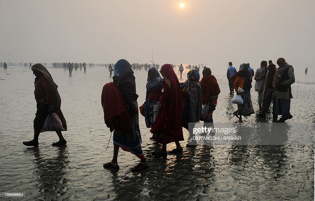 Hindu pilgrims walk back to the camp after performing prayers at the Gangasagar island, around 160 kms south of Kolkata on January 13, 2013. Sadhus and Hindu piligrims from all over the country come for the annual Hindu holy festival Gangasagar Mela, with more than four hundred thousand Hindu pilgrims gathering at the Gangasagar to take a 'holy dip' in the ocean at the confluence of the River Ganges and the Bay of Bengal on the occasion of Makar Sankranti, a holy day of the Hindu calendar considered to be of great religious significance in Hindu mythology. AFP PHOTO/Dibyangshu SARKAR