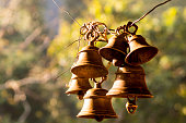 Hindu prayer bells in a remote temple in the forest with the bokeh of the trees and golden sunlight from a morning sun