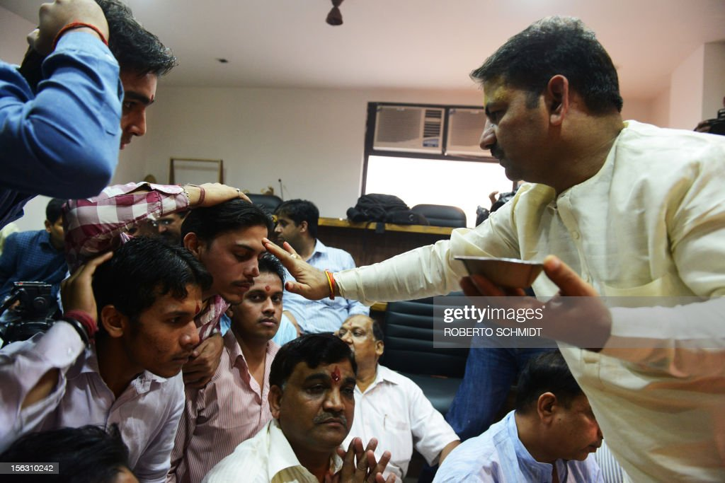 A Hindu priest blesses Indian members of a local trading organization by marking their forehead during a ceremony in which they worship electronic gadgets including iPads,laptops and mobile phones on Diwali, the Festival of Lights at their office in New Delhi on November 13, 2012. Since ages, the worshipping of account books has been an essential part of Diwali for the business community in India for prosperity of business. Signifying the modernisation of the retail trade in India, some traders are now including the worshipping of electronic gadgets. The festival of Diwali celebrates the victory of good over evil, light over darkness and knowledge over ignorance. AFP PHOTO/Roberto Schmidt
