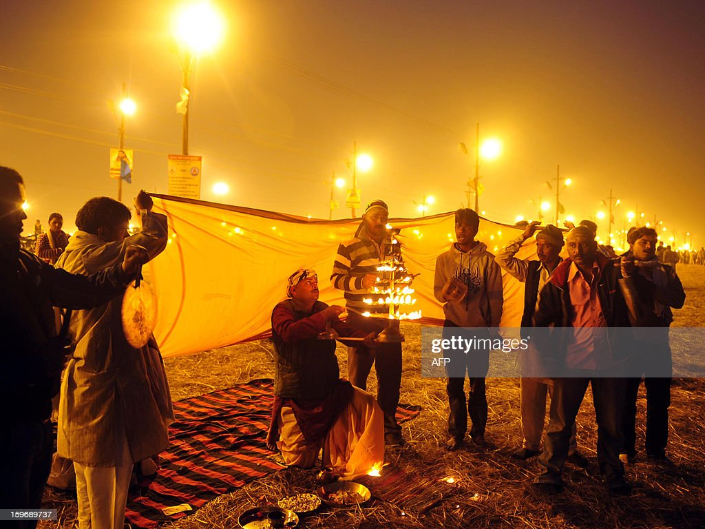 A Hindu priest (C) performs evening prayers at Sangam, the confluence of the Rivers Ganges, Yamuna and mythical Saraswati, during the Maha Kumbh Mela in Allahabad on January 18, 2013. The Kumbh Mela in the Indian town of Allahabad will see up to 100 million worshippers gather over the next 55 days to take a ritual bath in the holy waters, believed to cleanse sins and bestow blessings. AFP PHOTO/ Sanjay KANOJIA