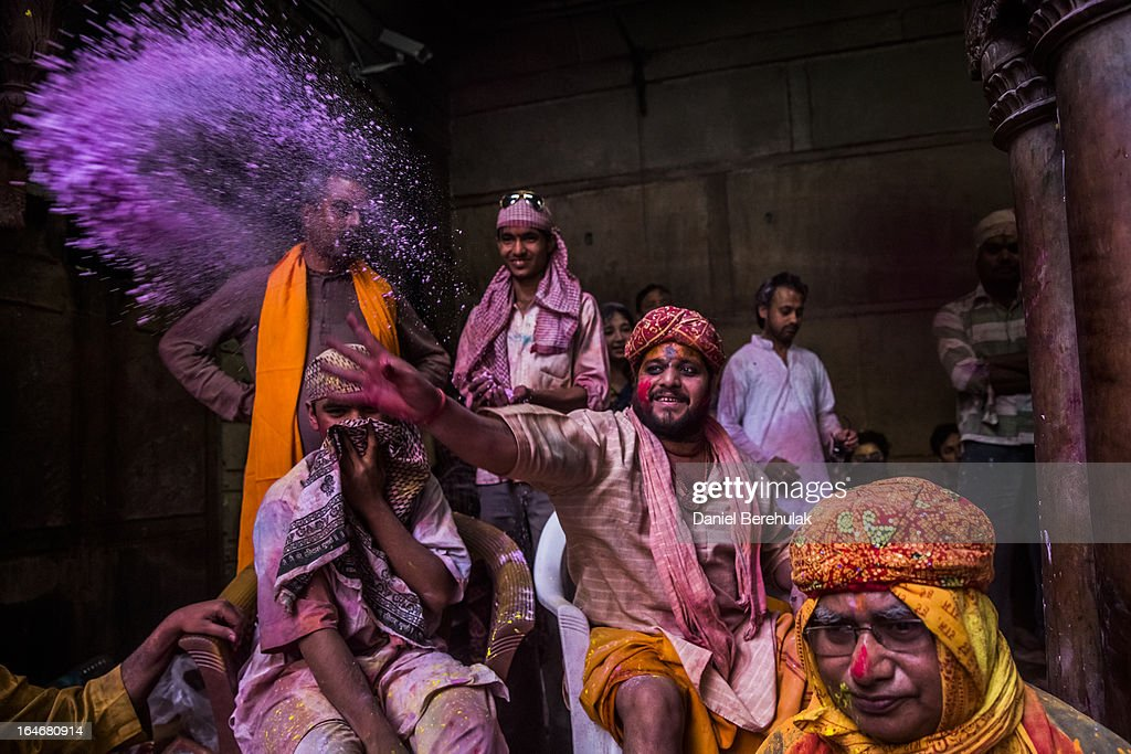 A Hindu priest throws coloured powder at devotees during Holi celebrations, at the Banke Bihari temple on March 26, 2013 in Vrindavan, India. The tradition of playing with colours on Holi draws its roots from a legend of Radha and the Hindu God Krishna. It is believed that young Krishna was jealous of Radha's fair complexion since he himself was very dark. After questioning his mother Yashoda on the darkness of his complexion, Yashoda, teasingly asked him to colour Radha's face in which ever colour he wanted. In a mischievous mood, Krishna applied colour on Radha's face. The tradition of applying color on one's beloved is being religiously followed till date.
