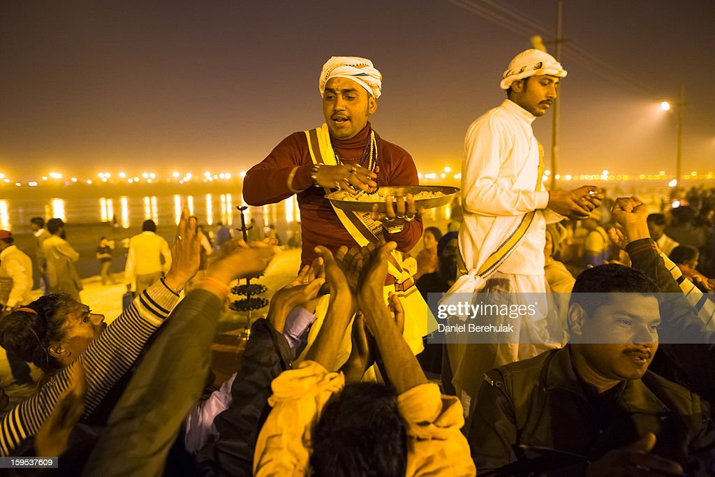Hindu priests distribute blessed sweets after an aarti ceremony on the banks of the Ganges river during the Maha Kumbh Mela on January 15, 2013 in Allahabad, India. The Maha Kumbh Mela, believed to be the largest religious gathering on earth is held every 12 years on the banks of Sangam, the confluence of the holy rivers Ganga, Yamuna and the mythical Saraswati. The Kumbh Mela alternates between the cities of Nasik, Allahabad, Ujjain and Haridwar every three years. The Maha Kumbh Mela celebrated at the holy site of Sangam in Allahabad, is the largest and holiest, celebrated over 55 days, it is expected to attract over 100 million people.