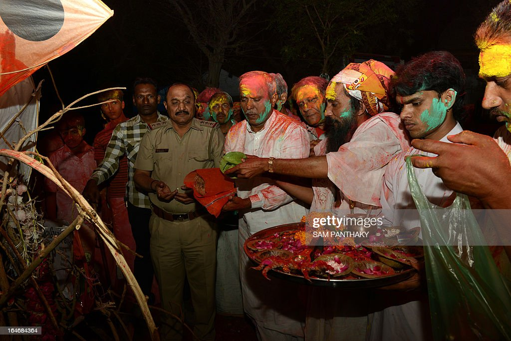 Hindu priests from Lord Jagannath Mandir and a police officer participate in a ritual before the Holika bonfire outside the Lord Jagannath Mandir in Ahmedabad on March 26, 2013. The priests from Lord Jagannath Mandir and the police officers together ignited Holika which symbolizes the destruction of evil, to mark Holi. AFP PHOTO / Sam PANTHAKY