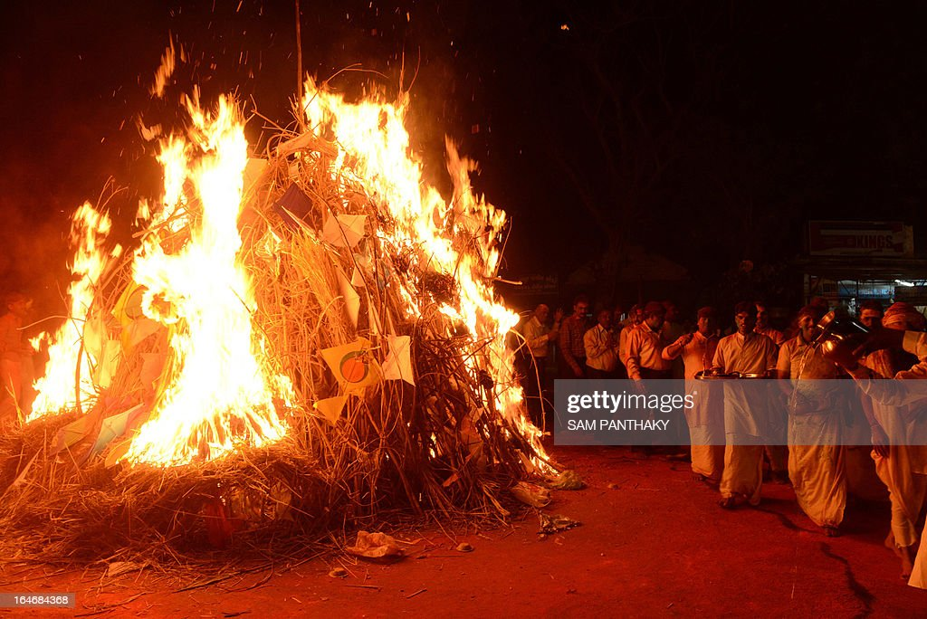Hindu priests from Lord Jagannath Mandir participate in a ritual around the Holika bonfire outside the Lord Jagannath Mandir in Ahmedabad on March 26, 2013. The priests from Lord Jagannath Mandir and the police officers together ignited Holika which symbolizes the destruction of evil, to mark Holi. AFP PHOTO / Sam PANTHAKY