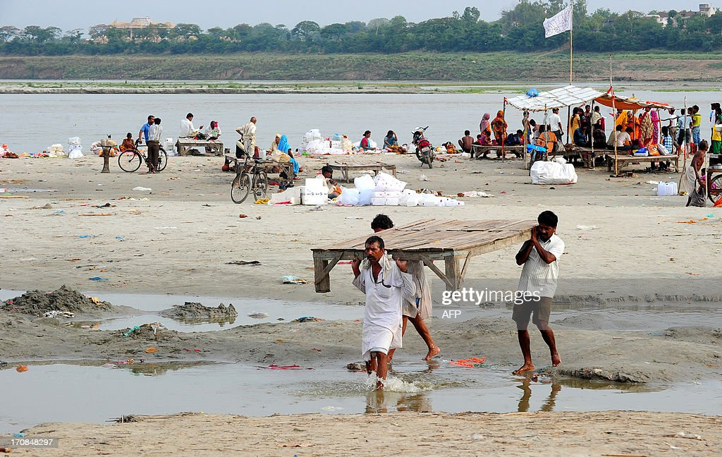 Hindu priests of the Sangam move their shelters from the banks of the Ganga river as the water level of the Ganga and Yamuna rises in Allahabad on June 19, 2013. Military helicopters dropped emergency supplies June 19 to thousands of tourists and pilgrims stranded by flash floods that tore through towns and temples in northern India, killing at least 138 people, officials said. The monsoon, which covers the subcontinent from June to September, usually brings some flooding but the heavy rains arrived early this year. AFP PHOTO / SANJAY KANOJIA