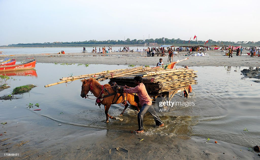 Hindu priests of the Sangam move their shelters from the banks of the Ganga river as the water level of the Ganga and Yamuna rises in Allahabad on June 19, 2013. Military helicopters dropped emergency supplies June 19 to thousands of tourists and pilgrims stranded by flash floods that tore through towns and temples in northern India, killing at least 138 people, officials said. The monsoon, which covers the subcontinent from June to September, usually brings some flooding but the heavy rains arrived early this year.