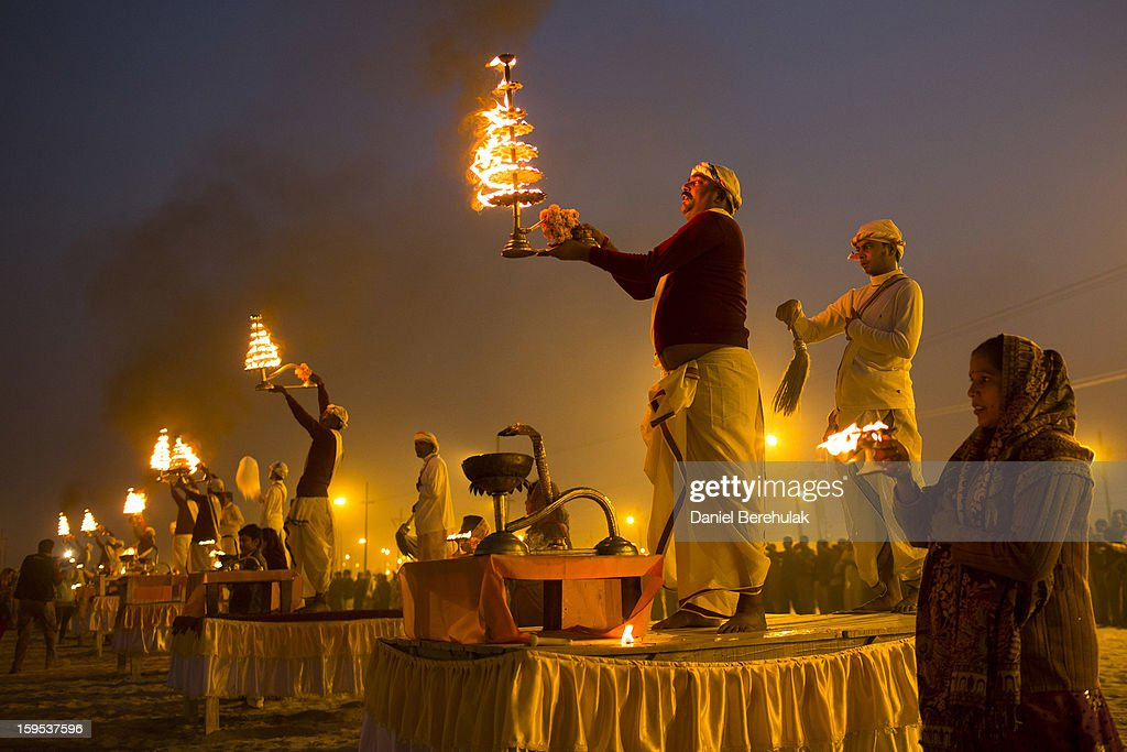 Hindu priests perform during an aarti ceremony on the banks of the Ganges river during the Maha Kumbh Mela on January 15, 2013 in Allahabad, India. The Maha Kumbh Mela, believed to be the largest religious gathering on earth is held every 12 years on the banks of Sangam, the confluence of the holy rivers Ganga, Yamuna and the mythical Saraswati. The Kumbh Mela alternates between the cities of Nasik, Allahabad, Ujjain and Haridwar every three years. The Maha Kumbh Mela celebrated at the holy site of Sangam in Allahabad, is the largest and holiest, celebrated over 55 days, it is expected to attract over 100 million people.