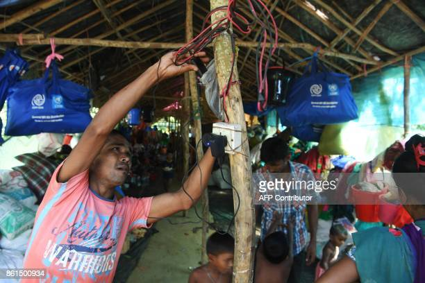 A Hindu refugee from Rakhine state charges his mobile phone at the Kutupalong Hindu refugee camp in the Bangladeshi district of Ukhia on October 15...