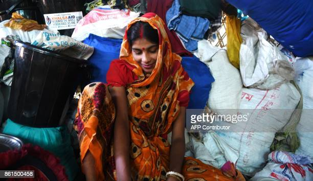 A Hindu refugee from Rakhine state smiles as she is photographed inside her makeshift hut at the Kutupalong Hindu refugee camp in the Bangladeshi...