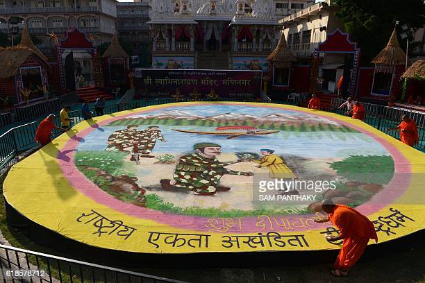 TOPSHOT Hindu religious men from the Swaminarayan Gadi Sansthan Maninagar put the final touches on a huge piece of folk art a Rangoli ahead of Diwali...