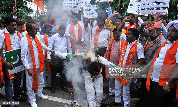 Hindu rightwing Shiv Sena activists burn an effigy and pictures of Pakistani Prime Minister Nawaz Sharif top and Pakistan's Prime Minister's Adviser...
