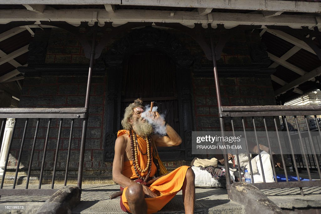A Hindu sadhu (holy man) smokes marijuana using a chillum, a traditional clay pipe, as a holy offering for Lord Shiva, the Hindu god of creation and destruction, near the Pashupatinath Temple in Kathmandu on February 20, 21013. Dozens of sadhus live around the temple devoting their life to Lord Shiva, the Hindu god of destruction. AFP PHOTO/Prakash MATHEMA