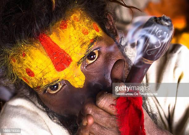 CONTENT] A hindu sadhu smoking hashish using a chillum at sunset at the hindu temple complex of Pashupatinath near Kathmandu