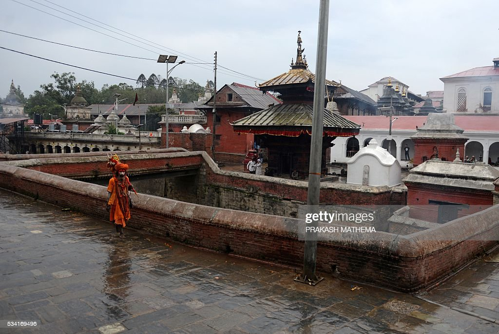Hindu Sadhu (holy men) walks by the Pashupatinath Temple in Kathmandu on May 25, 2016. Dozens of Sadhus live around the temple devoting their life to Lord Shiva, the Hindu god of destruction. / AFP / PRAKASH