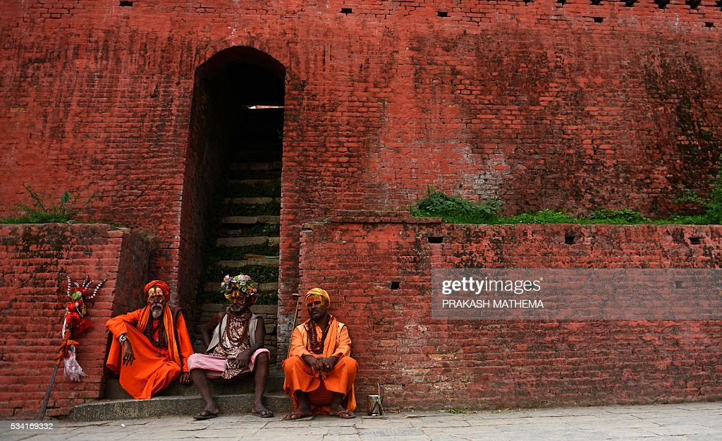 Hindu Sadhus (holy men) sit in open area of the premises of the Pashupatinath Temple in Kathmandu on May 25, 2016. Dozens of Sadhus live around the temple devoting their life to Lord Shiva, the Hindu god of destruction. / AFP / PRAKASH
