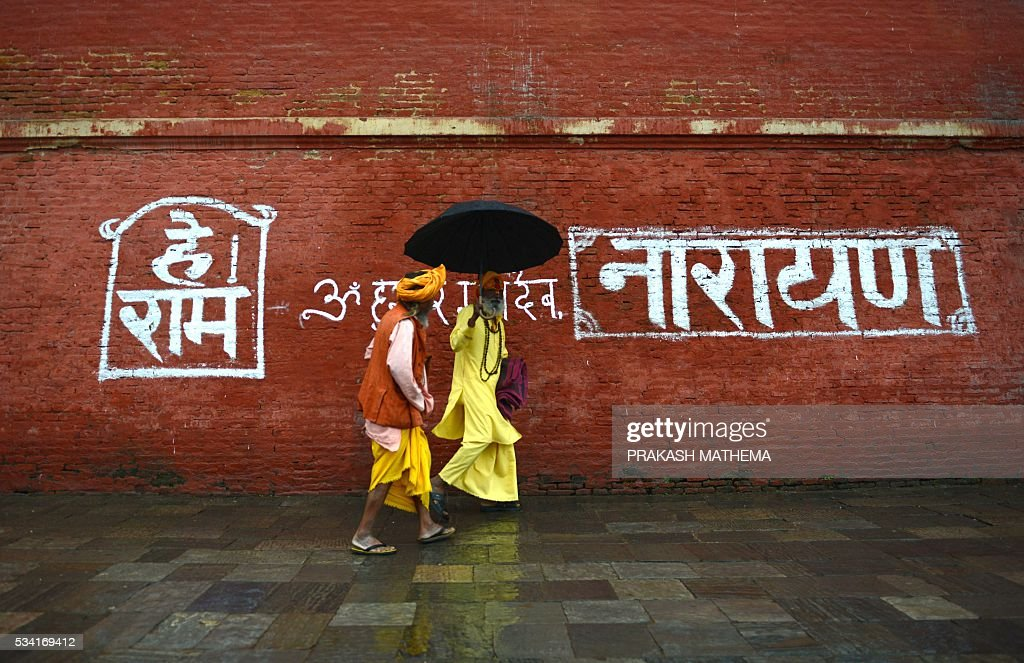 Hindu Sadhus (holy men) walk by the Pashupatinath Temple in Kathmandu on May 25, 2016. Dozens of Sadhus live around the temple devoting their life to Lord Shiva, the Hindu god of destruction. / AFP / PRAKASH