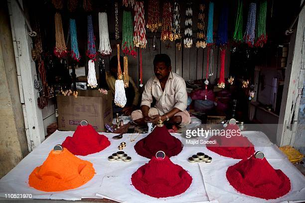 Hindu shop keeper is selling color during Holi celebrations at the Bankey Bihari Temple on March 21 2011 in Vrindavan India Holi is celebrated at the...