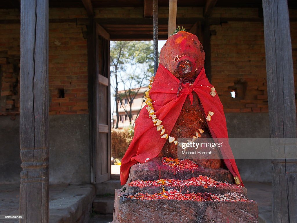 A Hindu shrine, a rock in the shape of Ganesh, is adorned with cloth and flowers in Bhaktapur, Nepal.